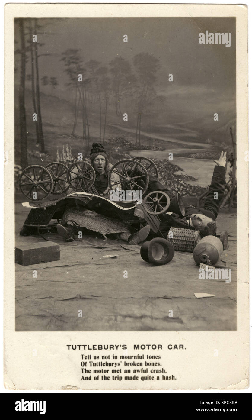Humorous staged motor accident photographed in a studio, with a man in drag collapsed under a makeshift car. 'Tell - Stock Image
