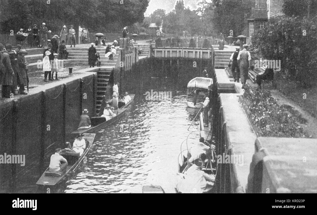 Some take to a boat on the river, others simply watch and stroll along the path at Boulters Lock on the River Thames, - Stock Image