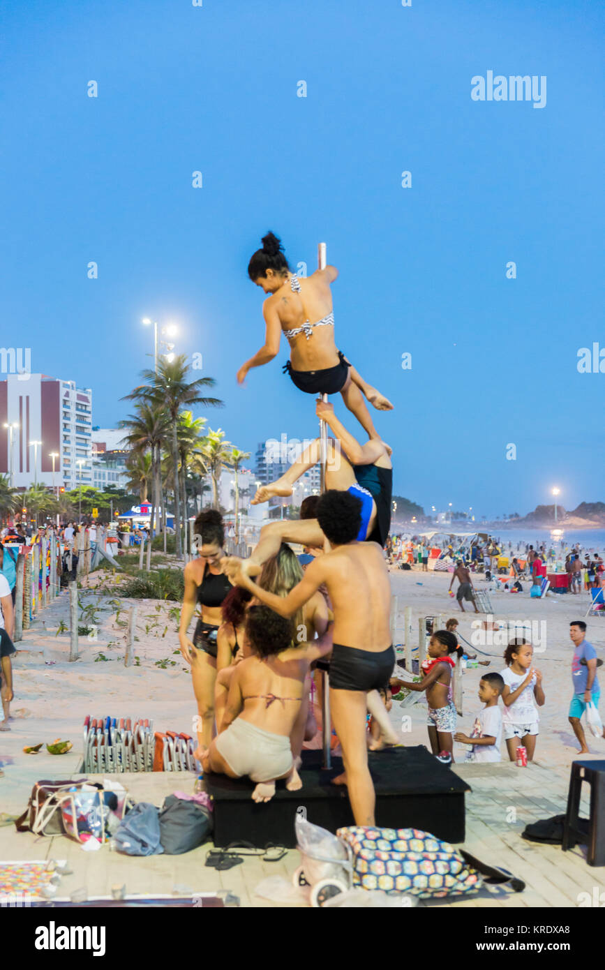 Pole dancers / athletes on a pole set up on Ipanema Beach in Rio de Janeiro, Brazil - a popular hobby for youngsters Stock Photo