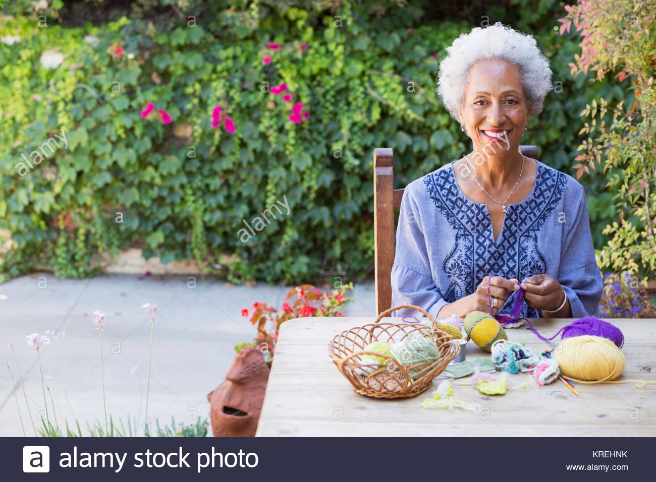 Black woman knitting outdoors - Stock Image