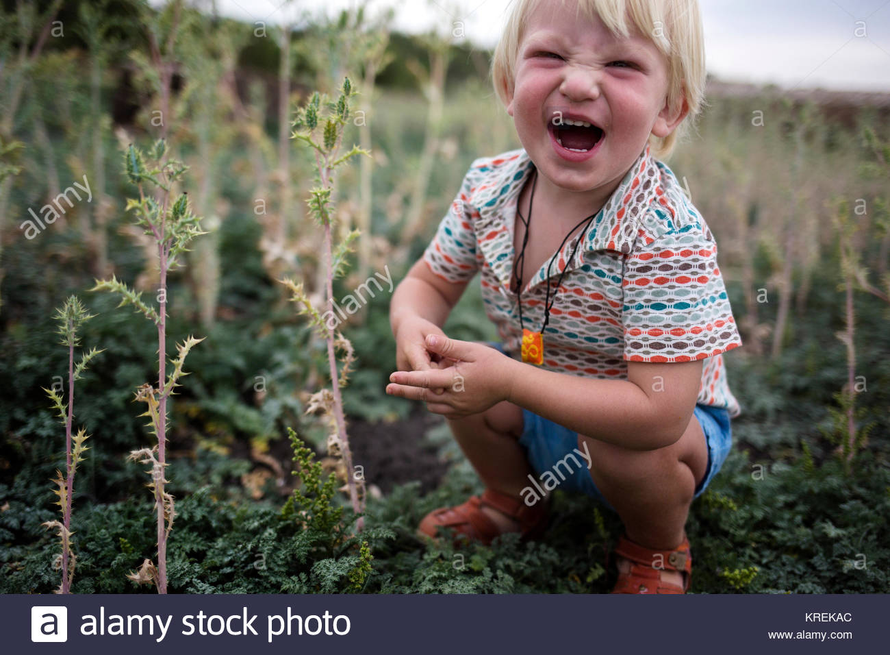 Laughing Caucasian boy crouching outdoors - Stock Image