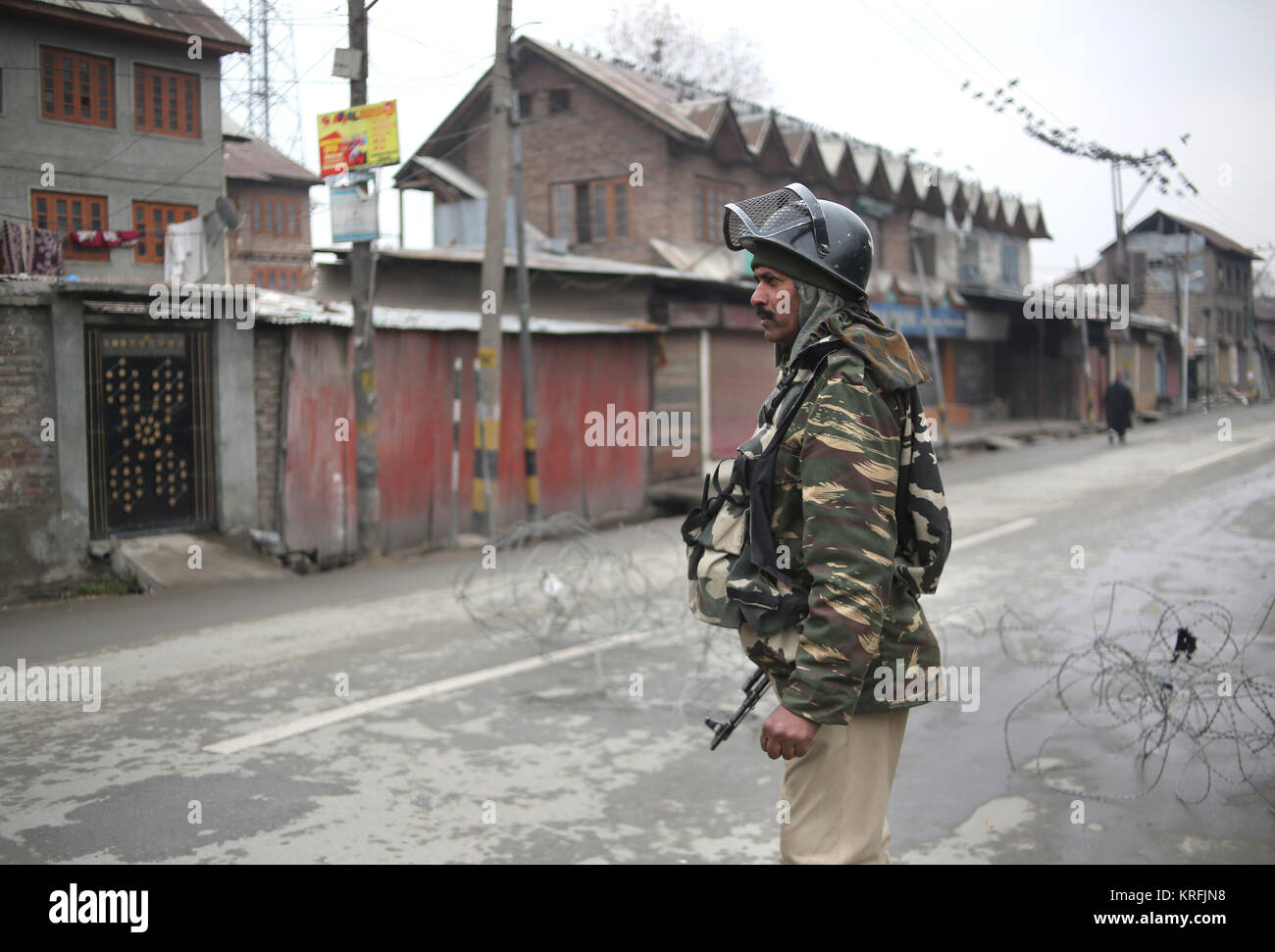 Srinagar, Kashmir. 20th Dec, 2017. An Indian paramilitary trooper stands guard on a road during restrictions in - Stock Image