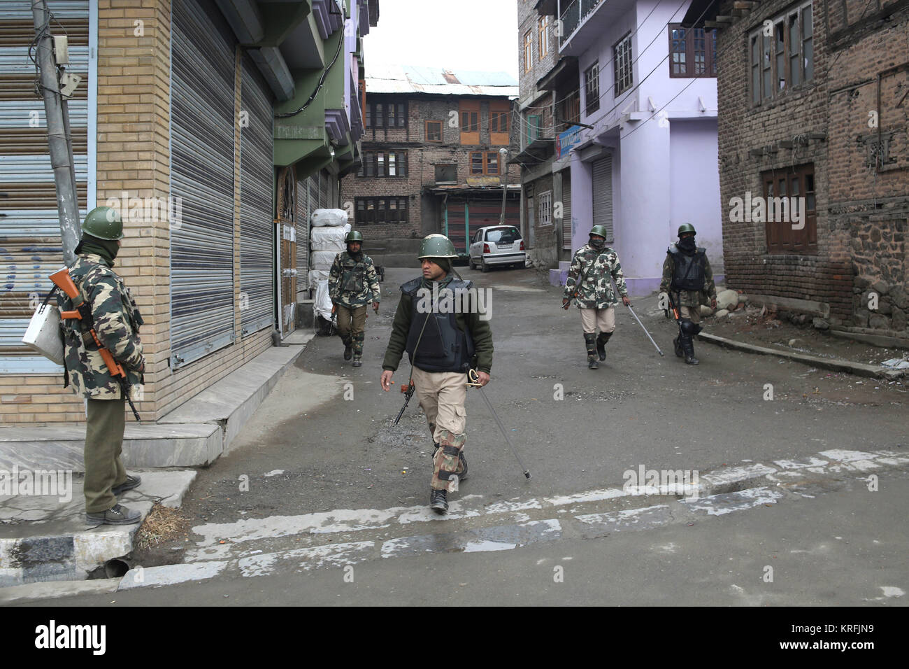 Srinagar, Kashmir. 20th Dec, 2017. Indian paramilitary troopers stand guard at a closed market during restrictions - Stock Image