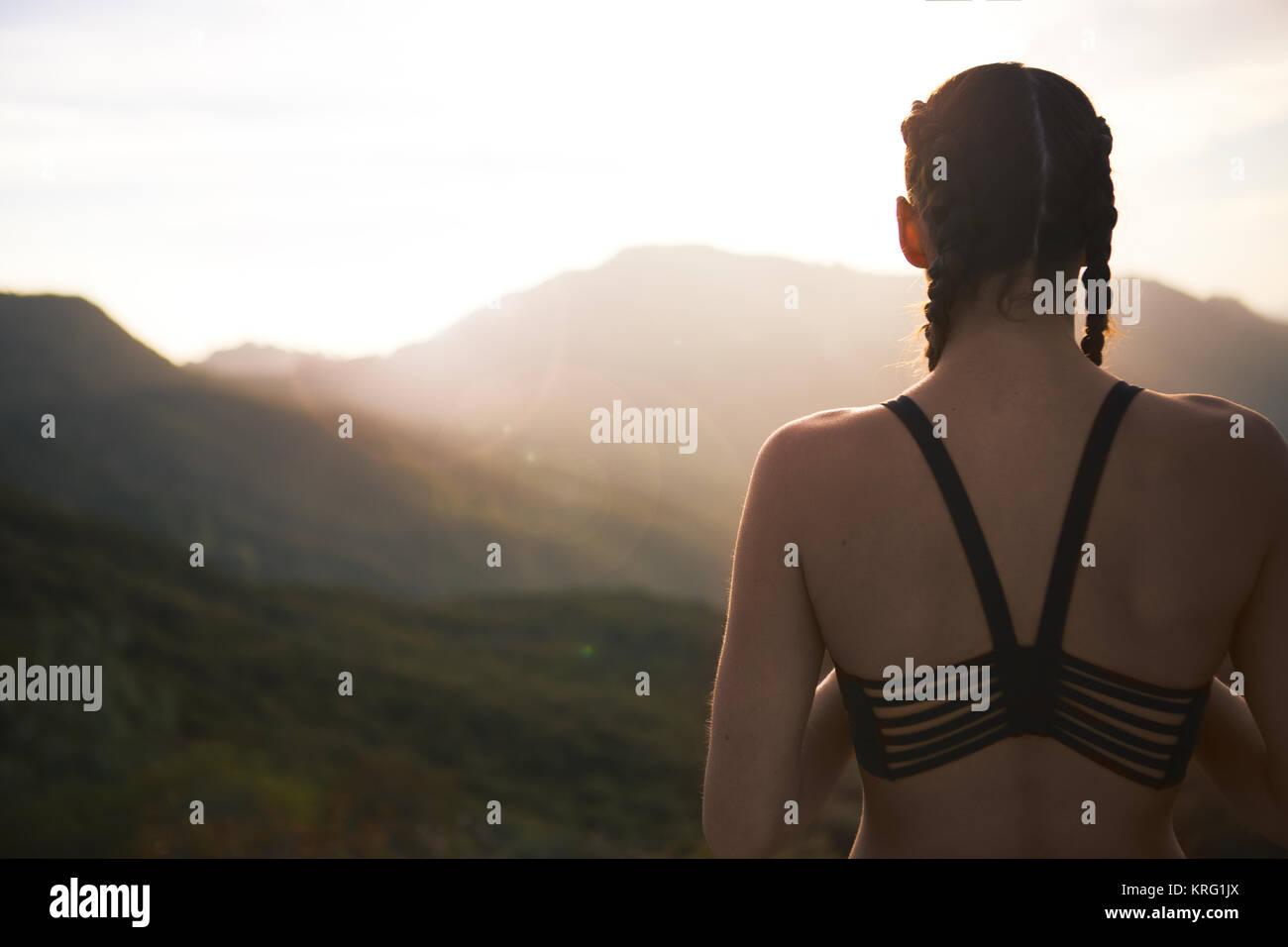 Female Athelete Overlooking Sunset - Stock Image