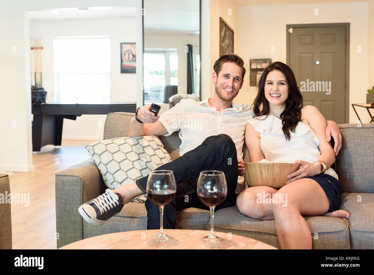 Smiling Caucasian couple sitting on sofa watching television - Stock Image