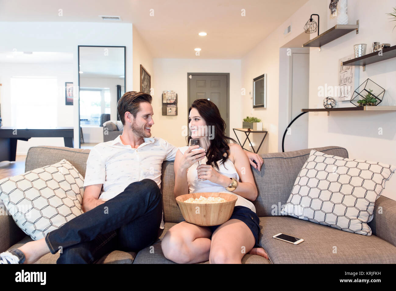 Smiling Caucasian couple relaxing on sofa with wine and popcorn - Stock Image