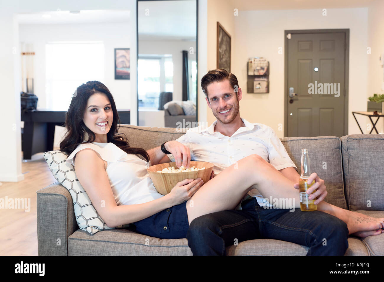 Smiling Caucasian couple relaxing on sofa with beer and popcorn - Stock Image