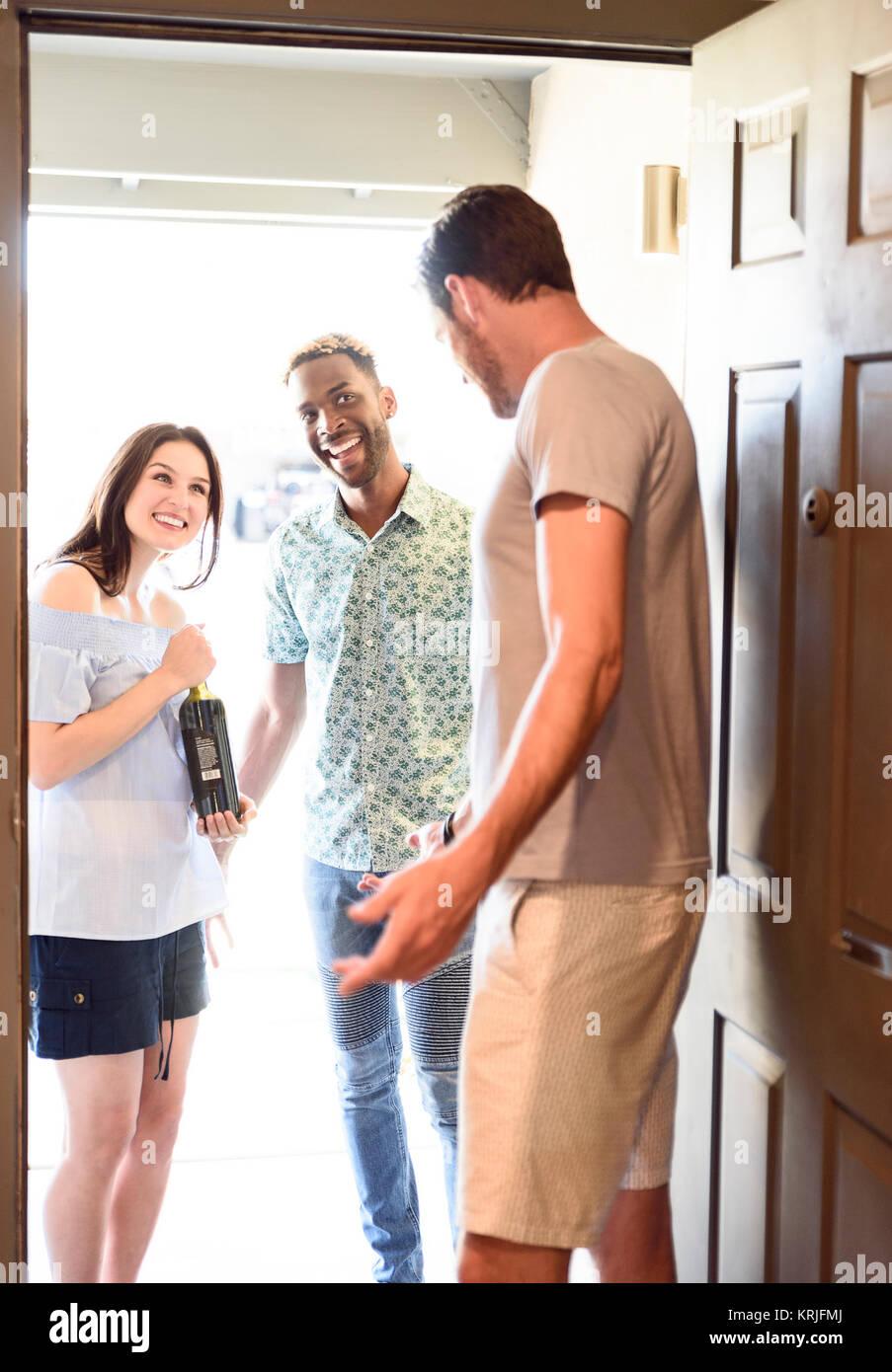 Man greeting couple bringing wine bottle at door - Stock Image