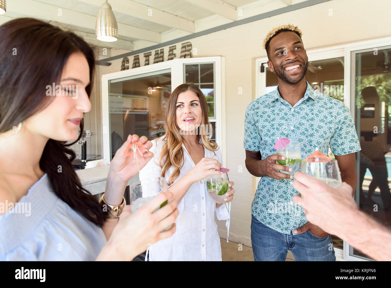 Smiling friends with cold drinks talking outdoors - Stock Image