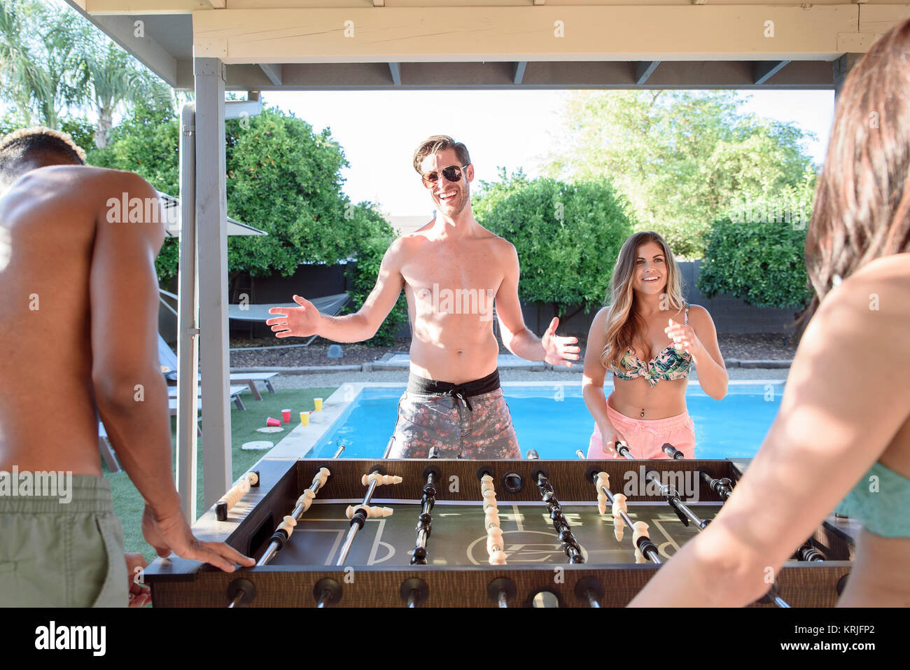 Friends playing foosball outdoors near swimming pool - Stock Image