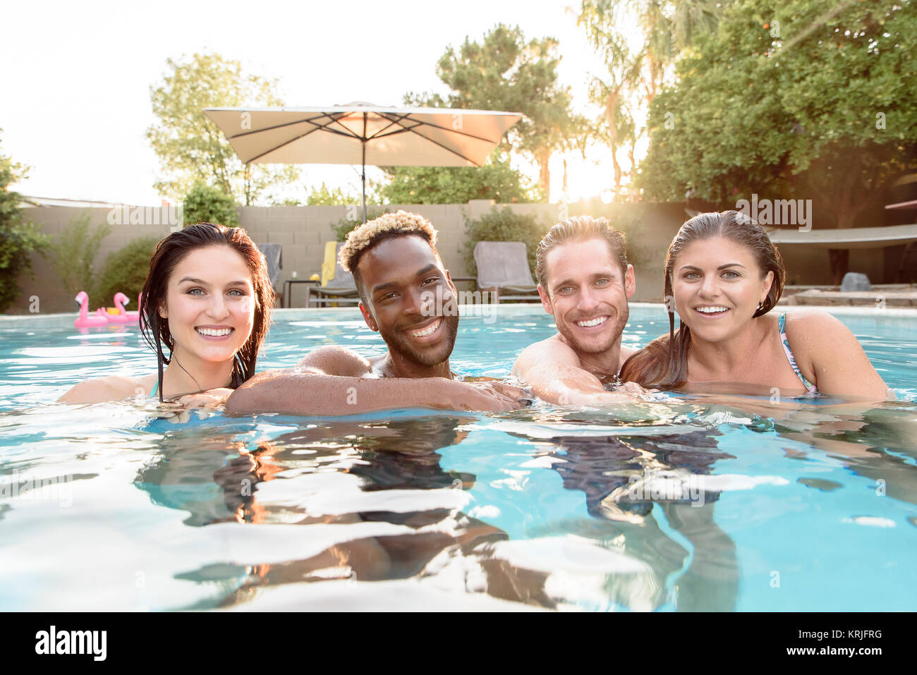 Portrait of smiling friends in swimming pool - Stock Image