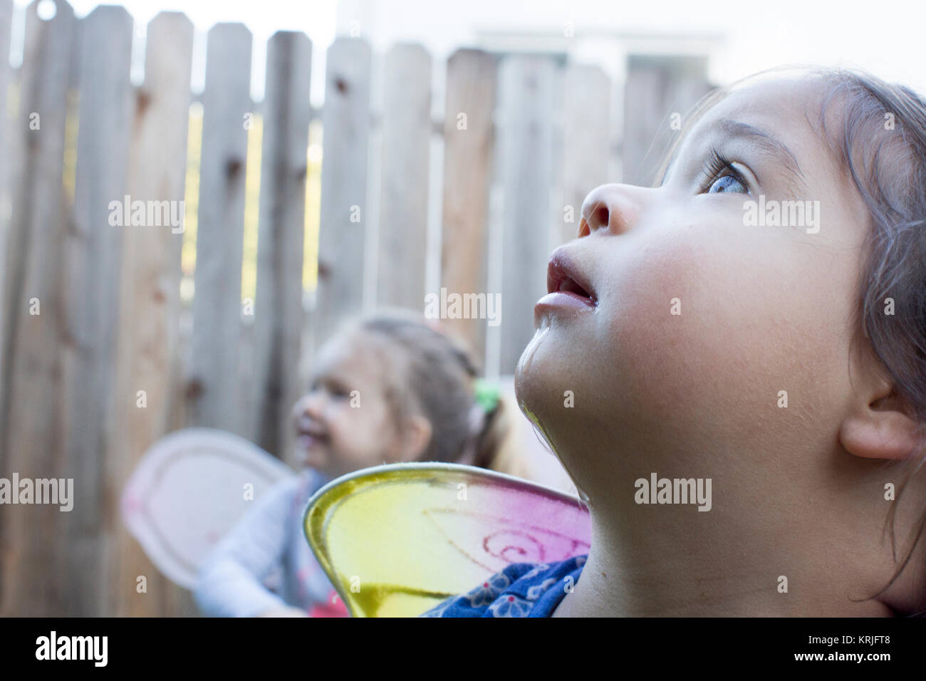 Curious girls wearing fairy wings outdoors - Stock Image