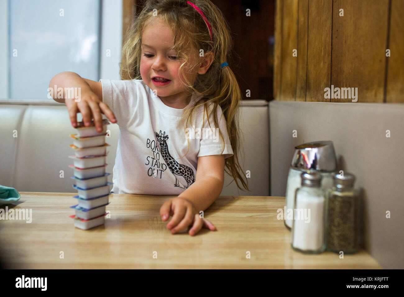 Smiling Caucasian girl stacking jelly containers in restaurant booth - Stock Image