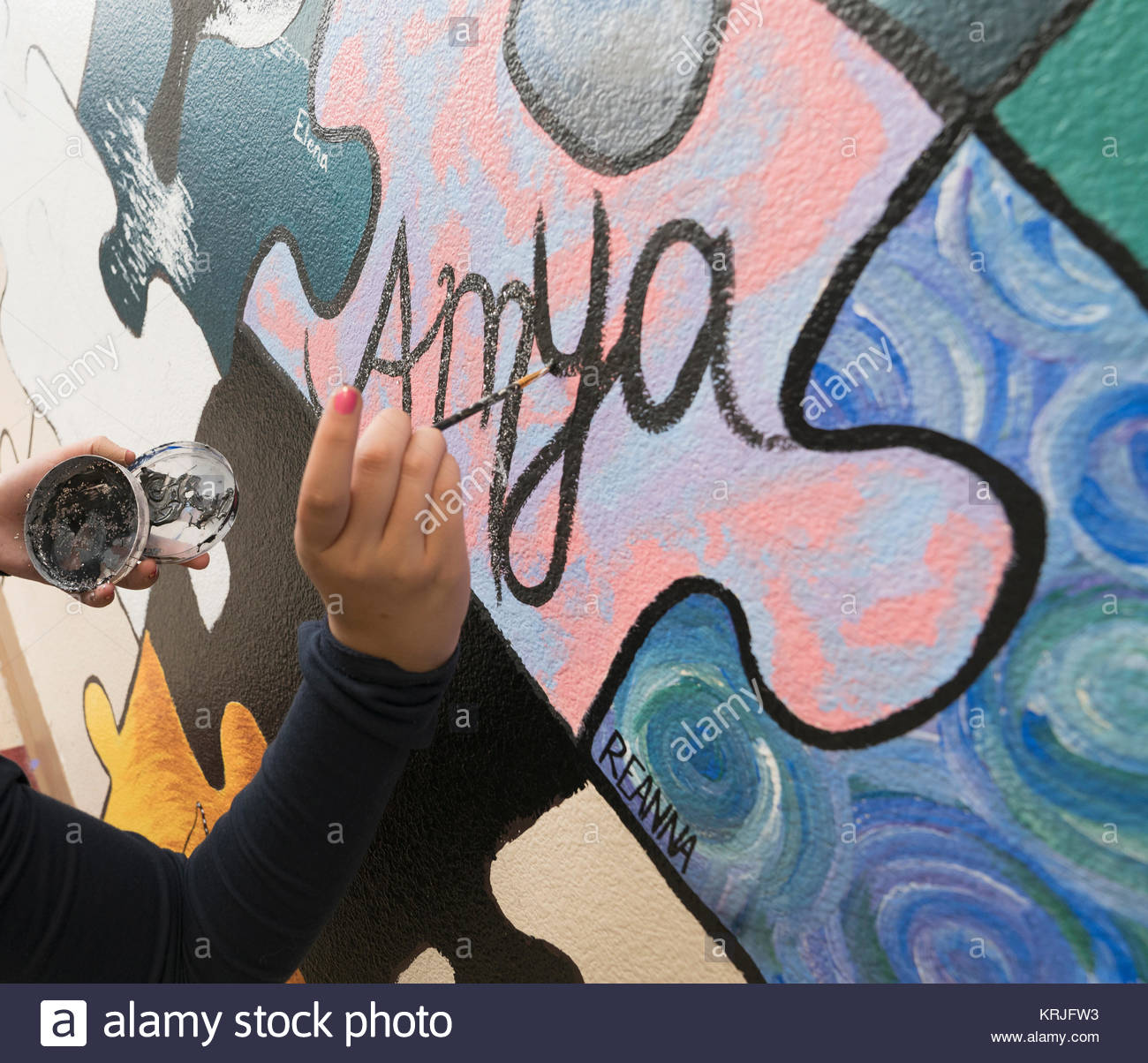 Hand of Caucasian girl painting mural on wall in school - Stock Image