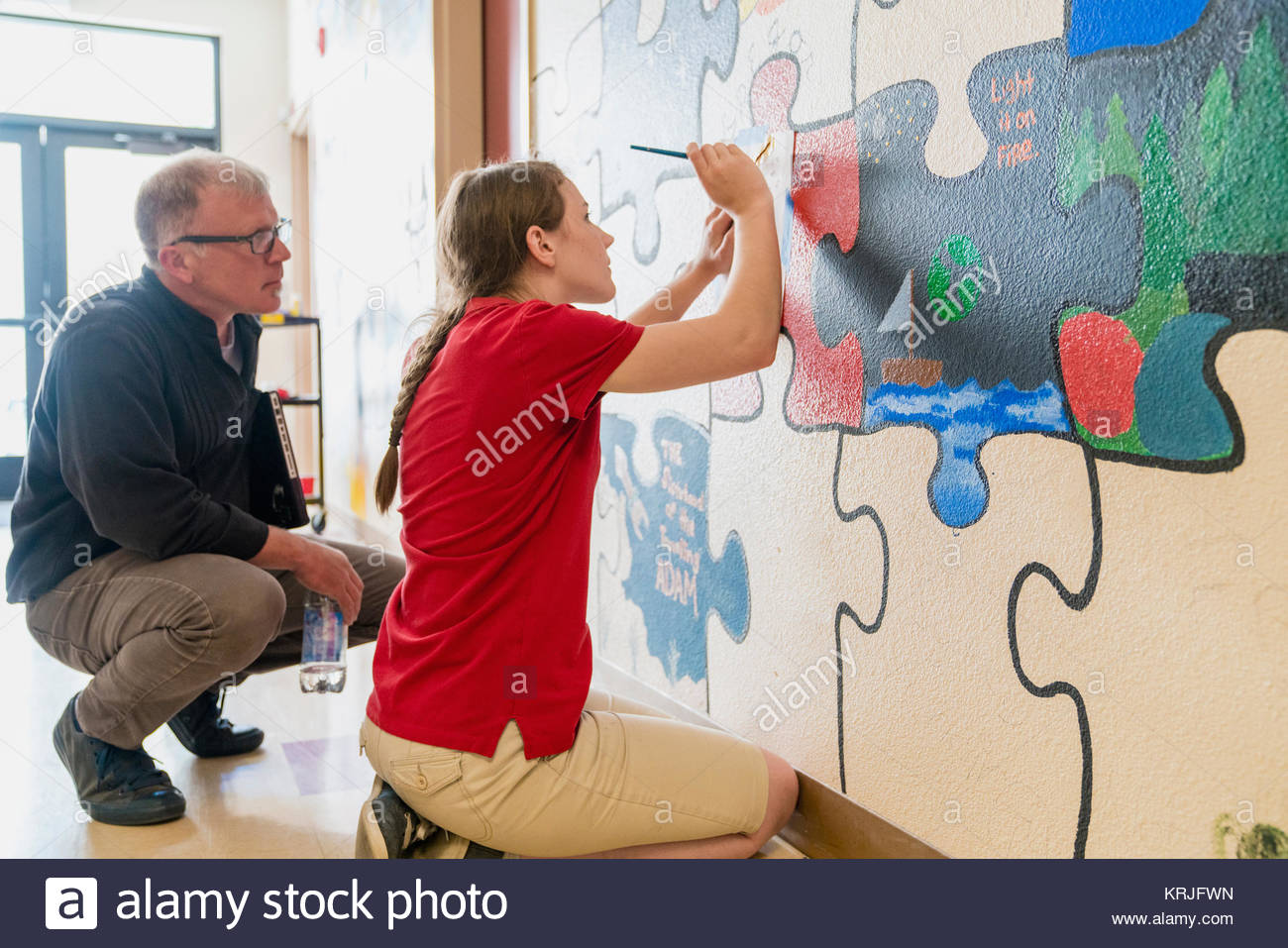 Teacher watching girl painting mural on wall at school - Stock Image