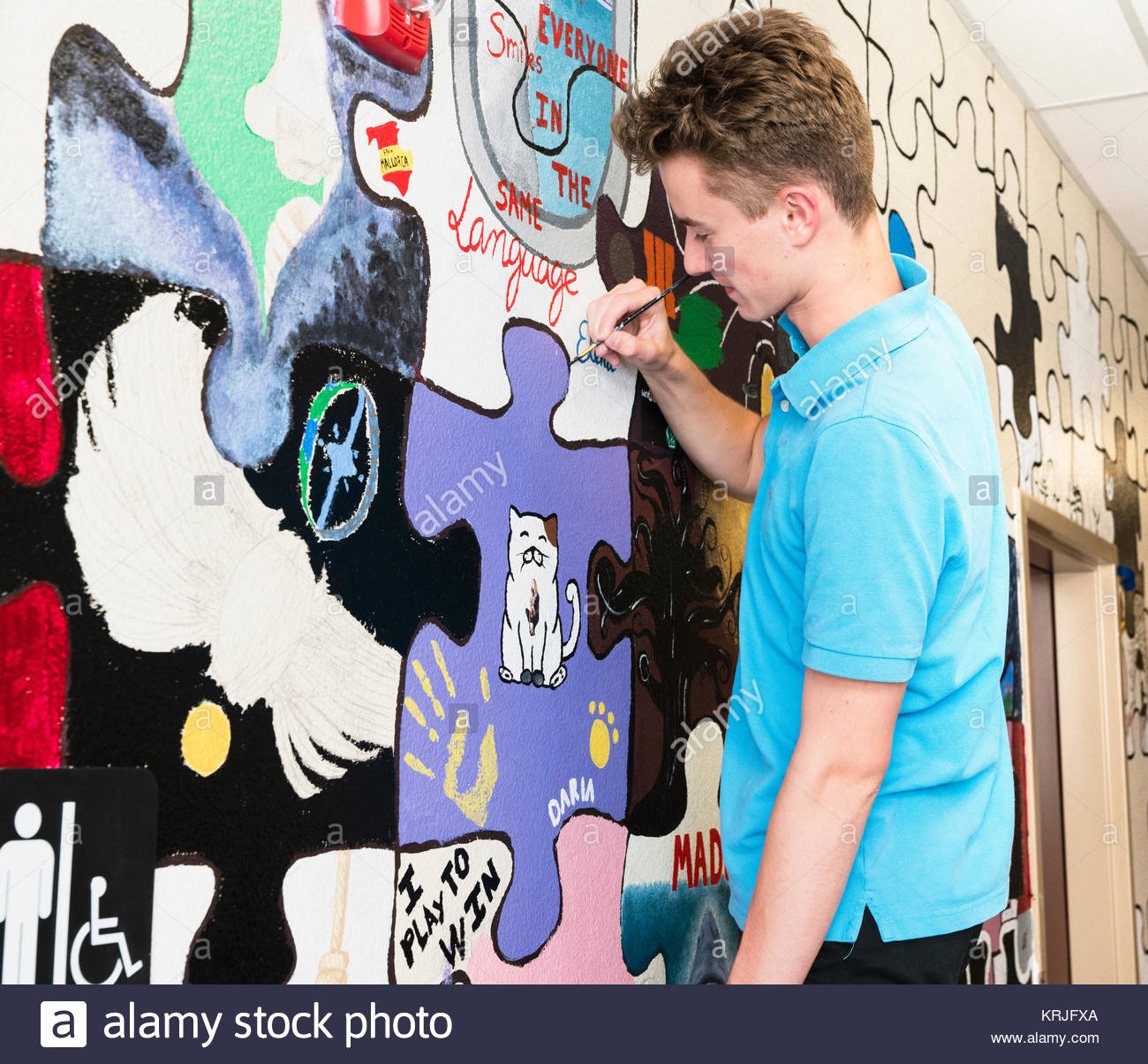 Caucasian boy painting mural on wall in school - Stock Image