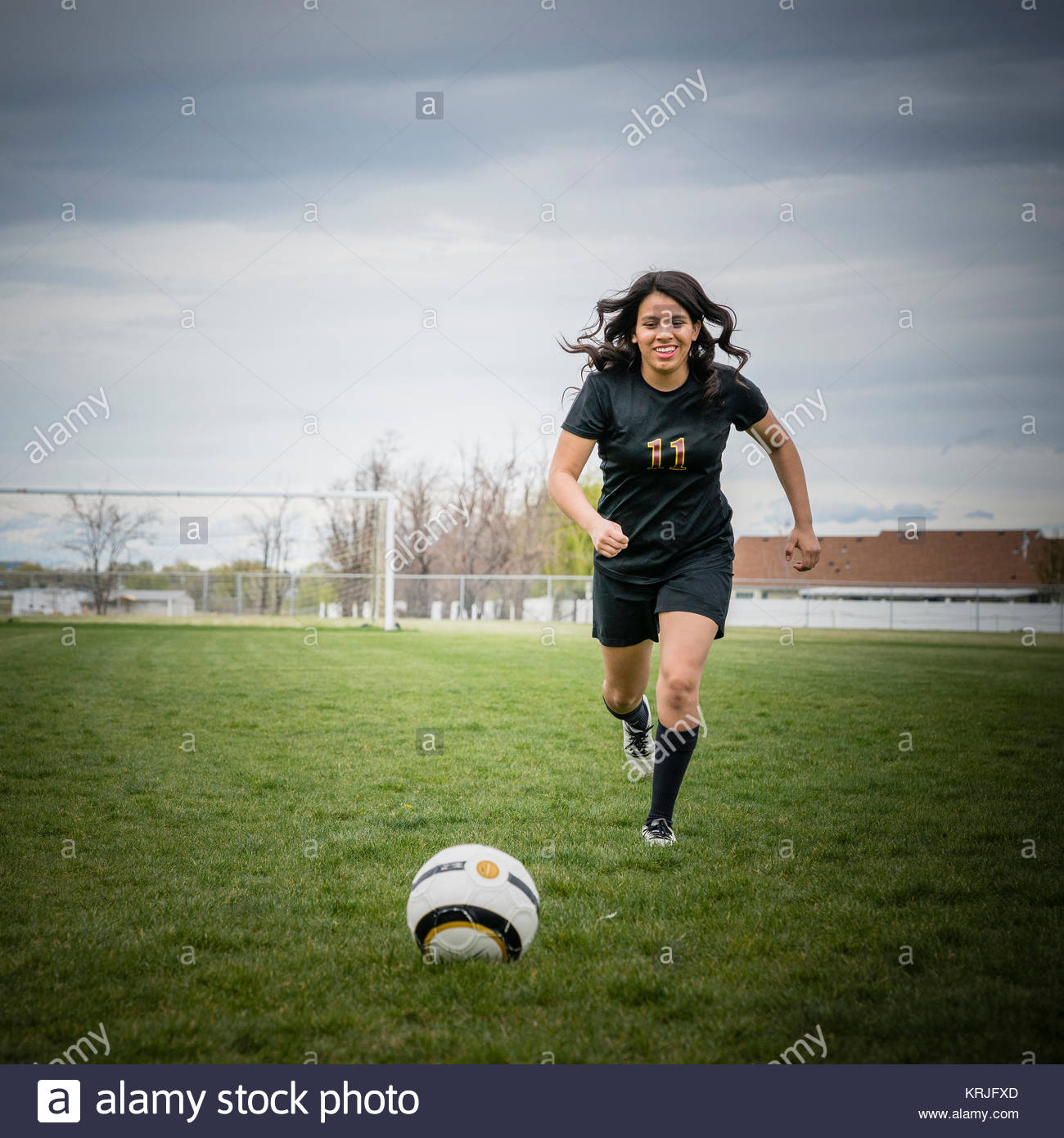 Smiling woman dribbling soccer ball in field - Stock Image