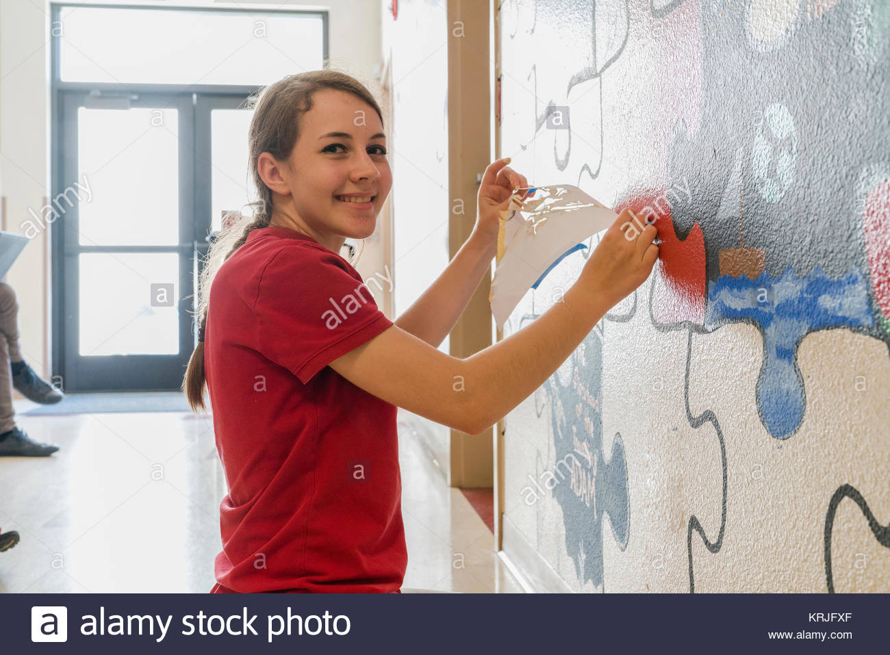 Portrait of Caucasian girl painting mural on wall in school with stencil - Stock Image