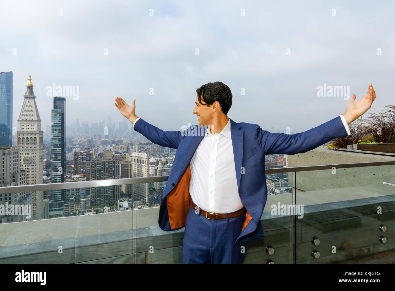 Caucasian businessman celebrating on urban rooftop - Stock Image