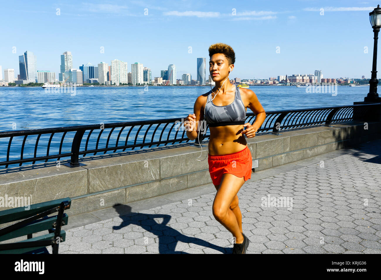 Mixed race woman running at waterfront listening to earbuds - Stock Image