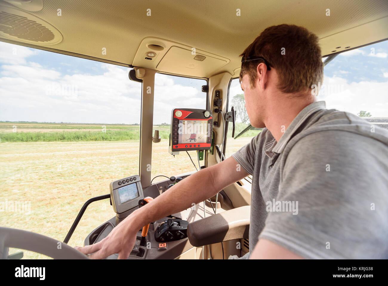 Caucasian man driving tractor on farm - Stock Image