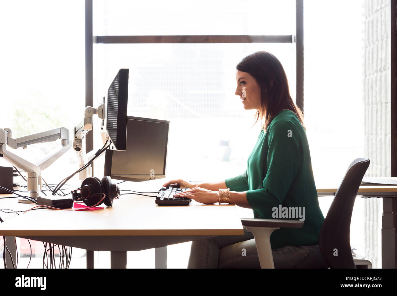 Caucasian woman using computer in office - Stock Image