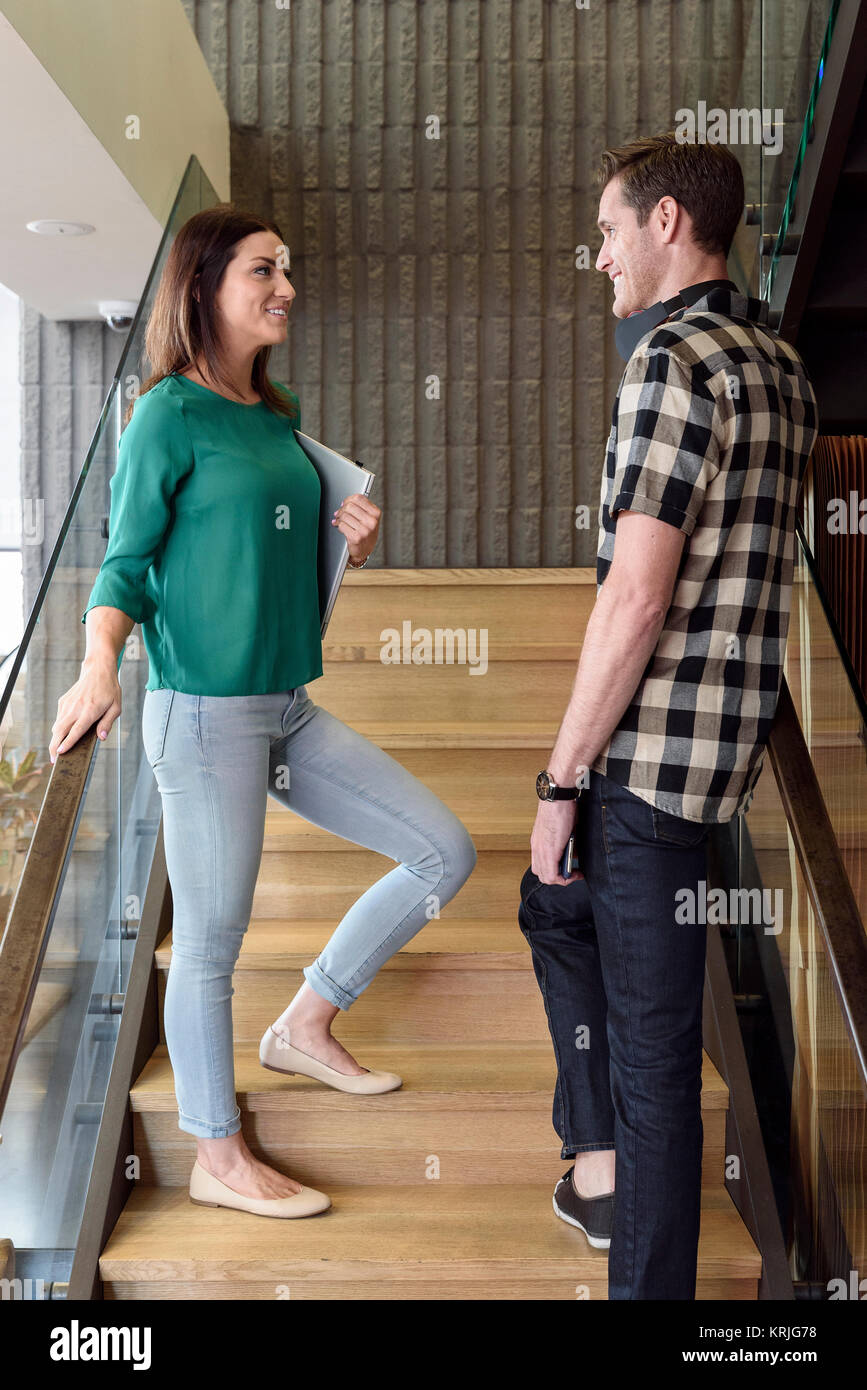 Caucasian man and woman talking on staircase - Stock Image