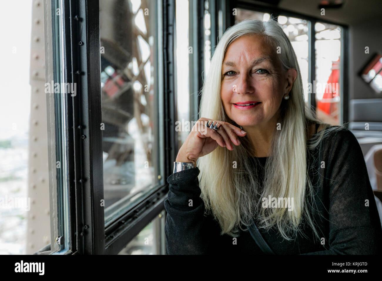 Portrait of smiling Caucasian woman near window - Stock Image