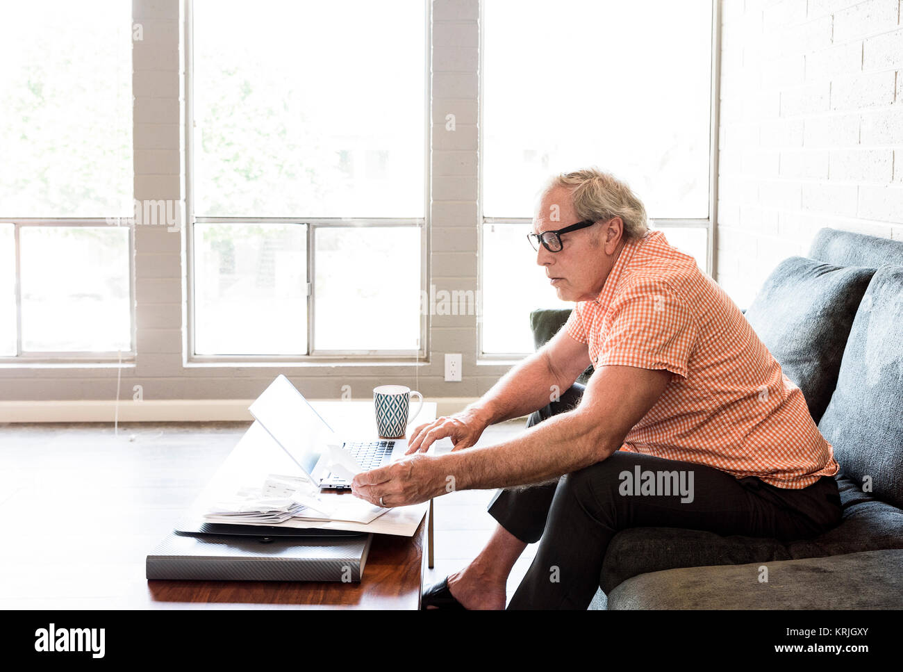 Caucasian man sitting on sofa paying bills with the laptop - Stock Image