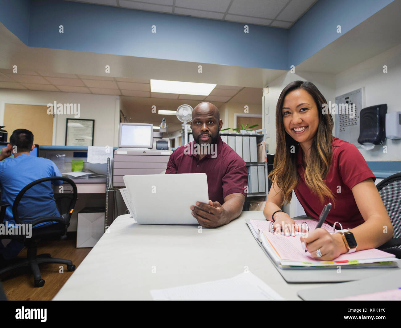 Portrait of smiling nurses with binders and hospital - Stock Image