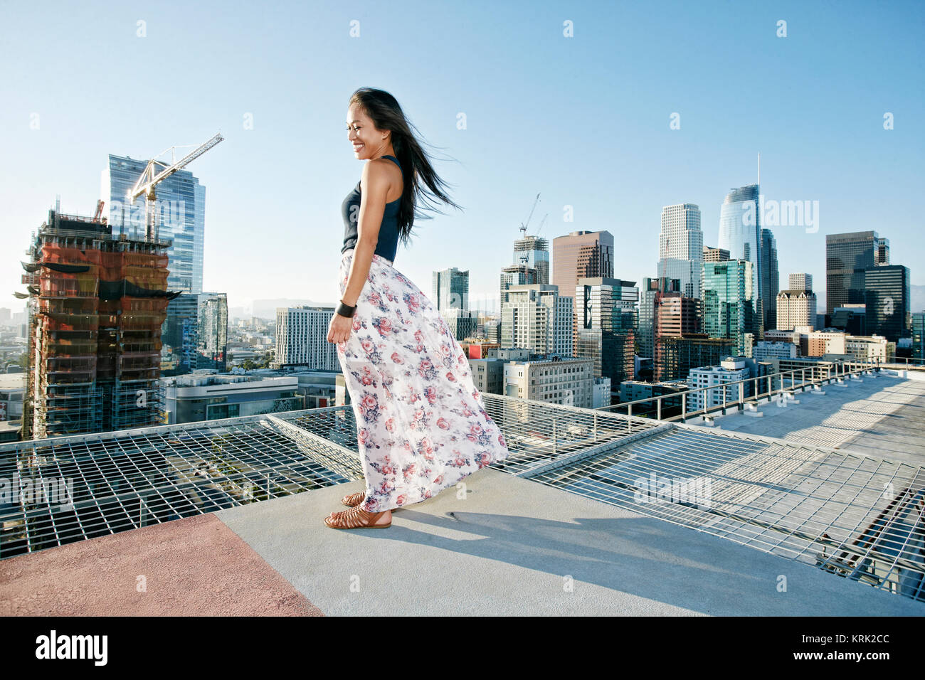 Smiling Asian woman standing on windy urban rooftop - Stock Image
