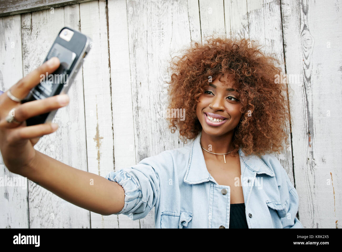 Black woman posing for cell phone selfie - Stock Image