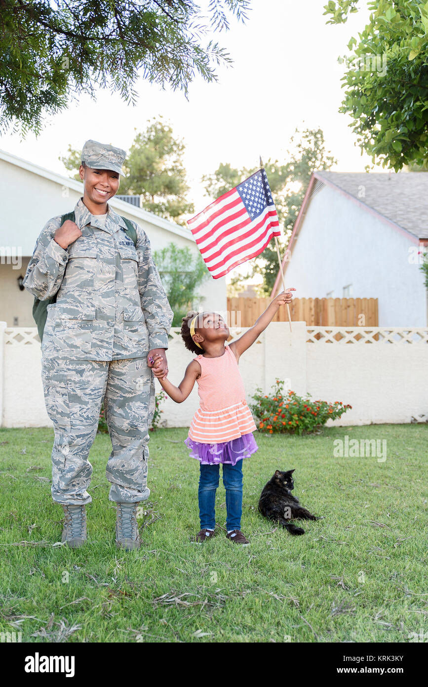 Smiling black woman soldier with daughter waving American flag - Stock Image