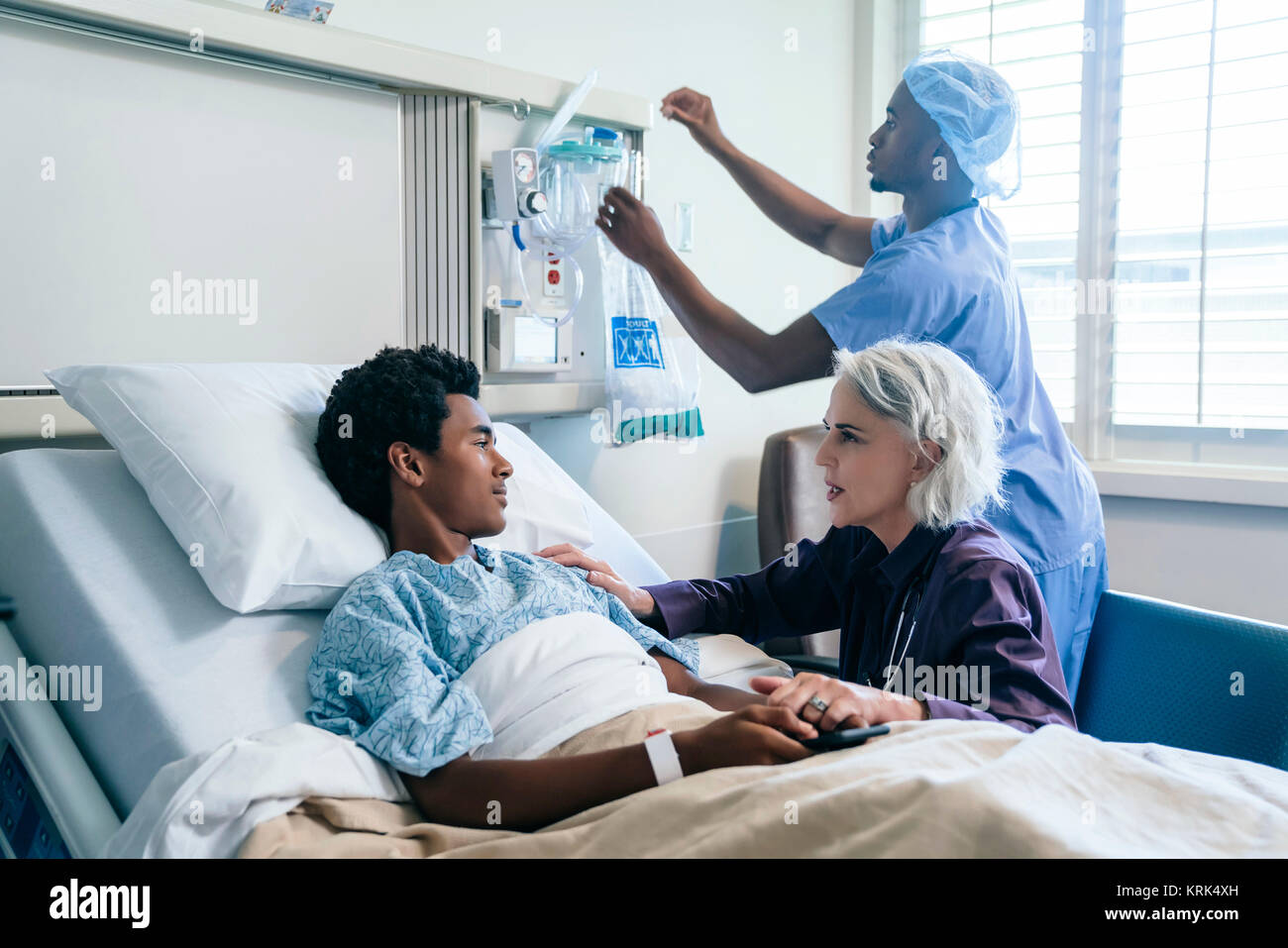 Doctor comforting boy laying in hospital bed - Stock Image