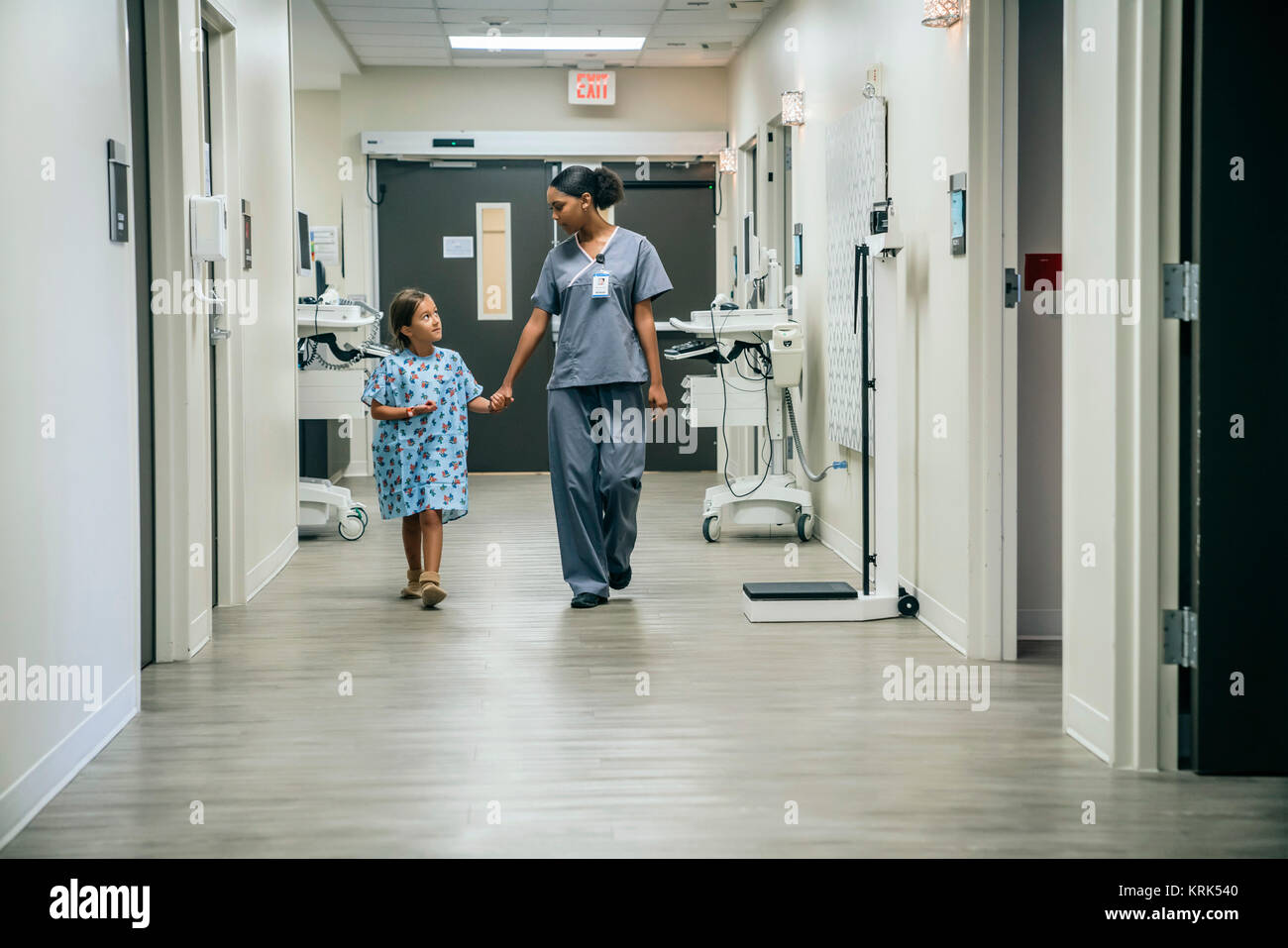 Nurse holding hands with girl in hospital - Stock Image
