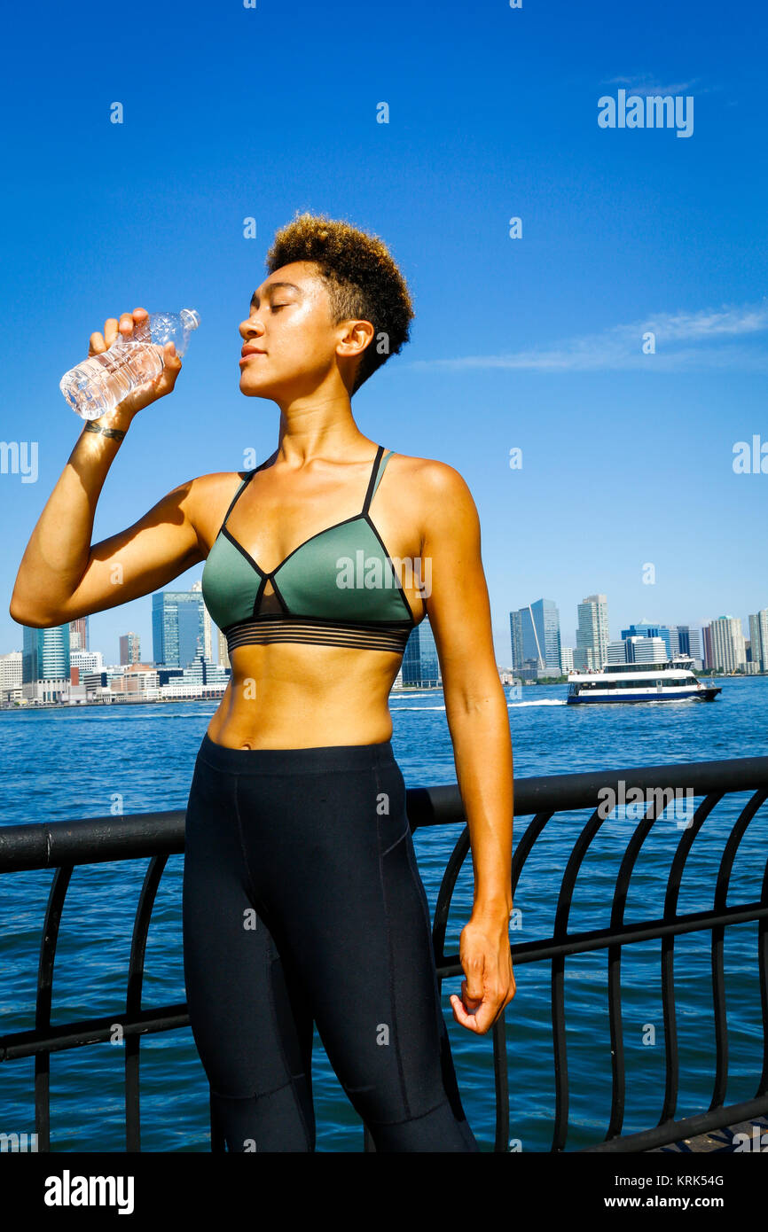 Mixed race woman drinking water at waterfront - Stock Image