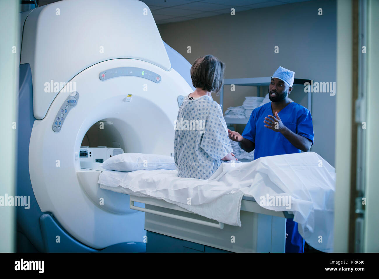 Technician talking to patient at scanner - Stock Image