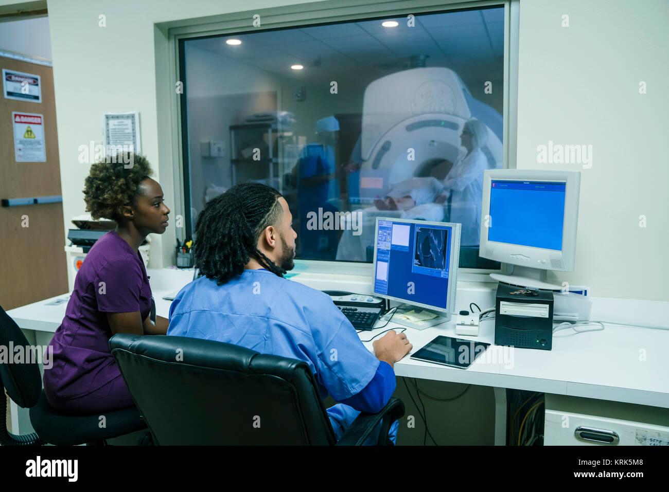 Nurses using computer near scanner - Stock Image