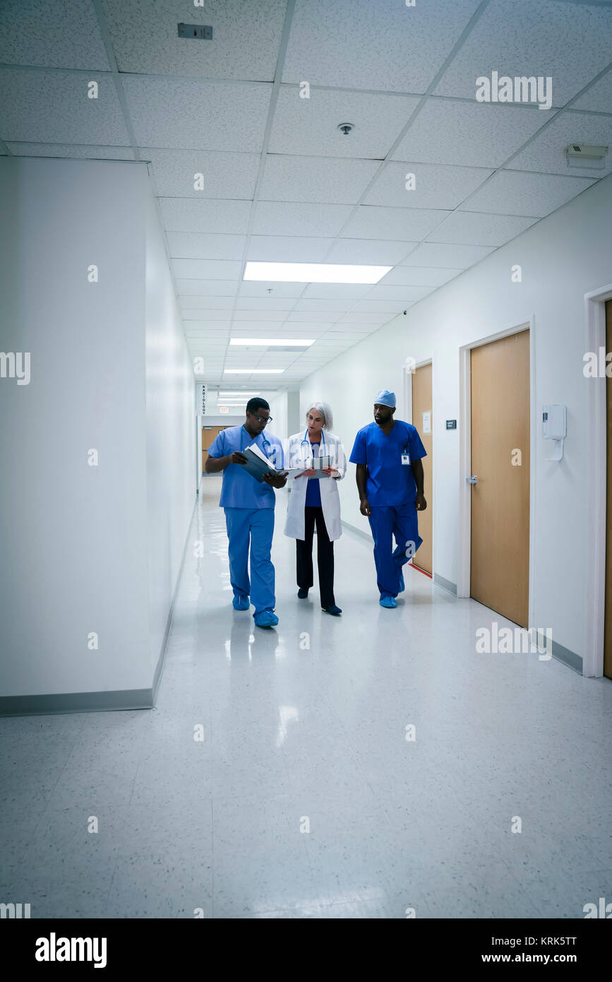 Doctor and nurses discussing paperwork in hospital - Stock Image