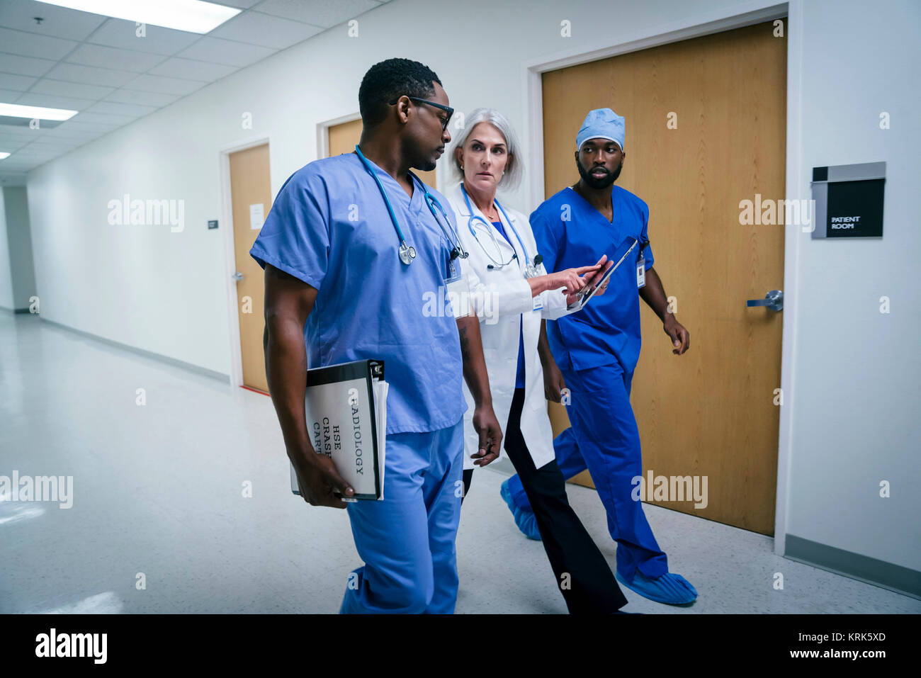 Doctor and nurses discussing digital tablet in hospital - Stock Image