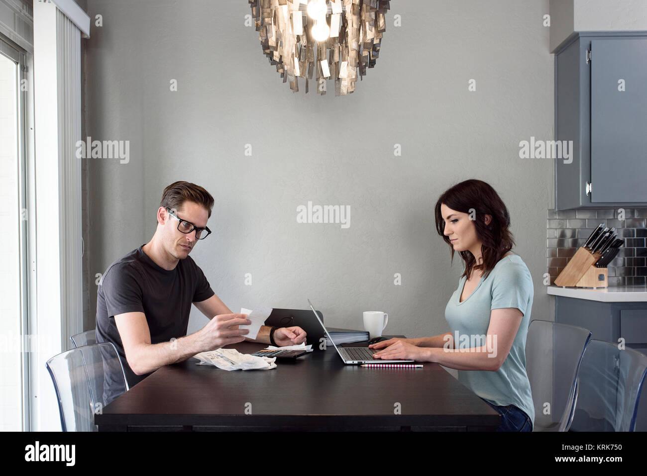 Caucasian man reading receipt while woman uses laptop - Stock Image