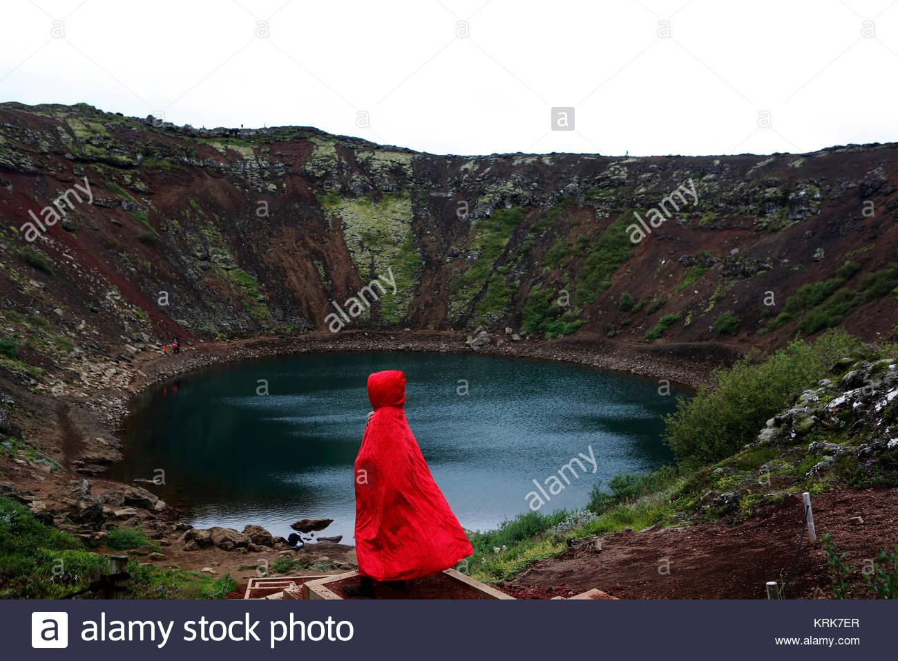 Caucasian woman wearing red robe at volcano lake - Stock Image
