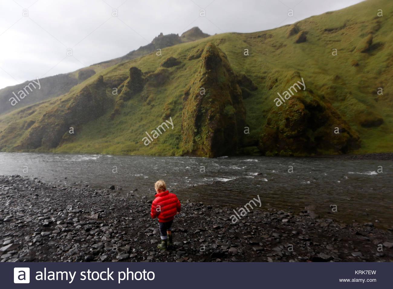 Caucasian boy was standing near rocky river - Stock Image