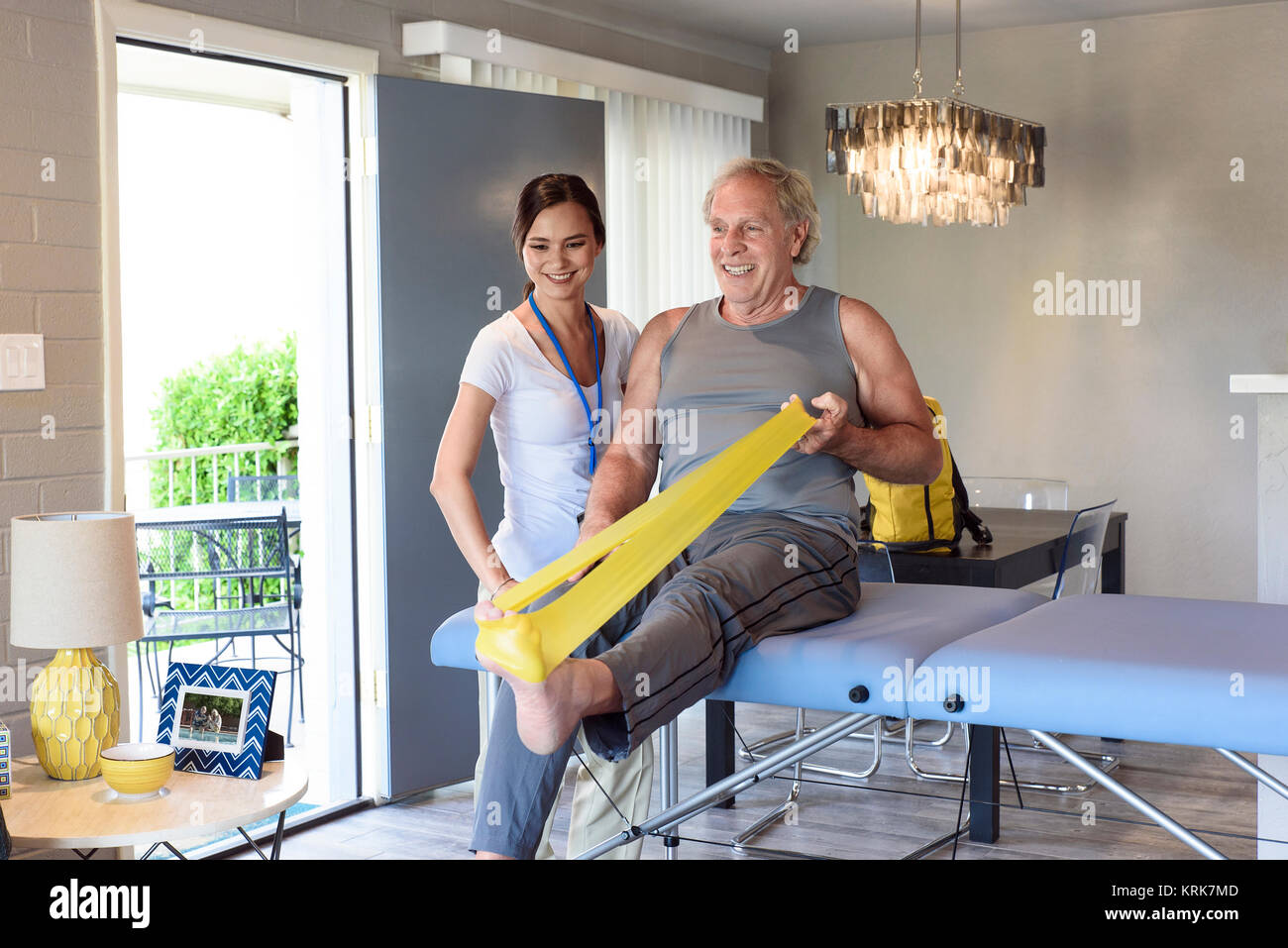 Physical therapist watching man stretch leg with resistance band - Stock Image