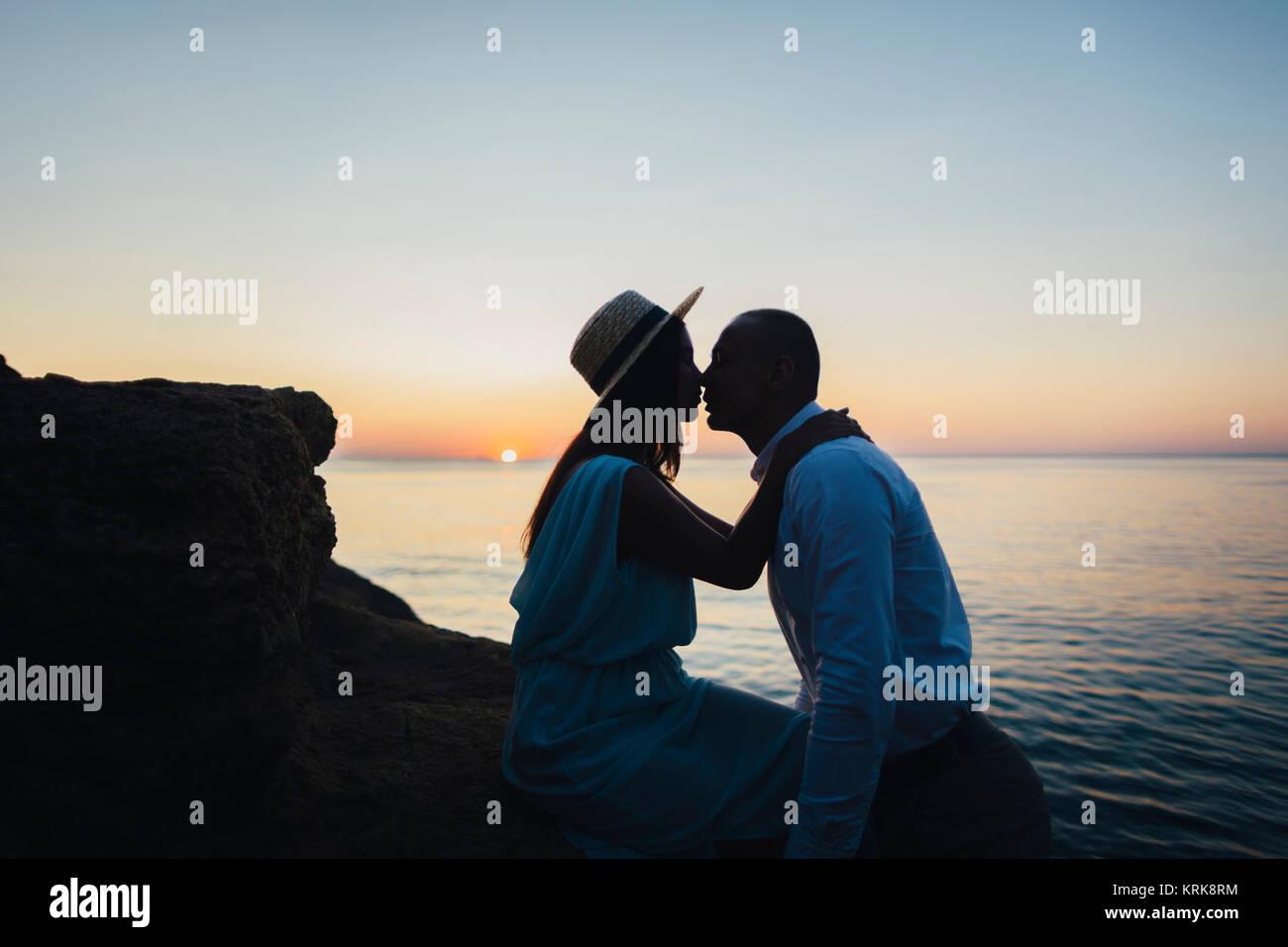Caucasian couple kissing on rock near ocean at sunset - Stock Image