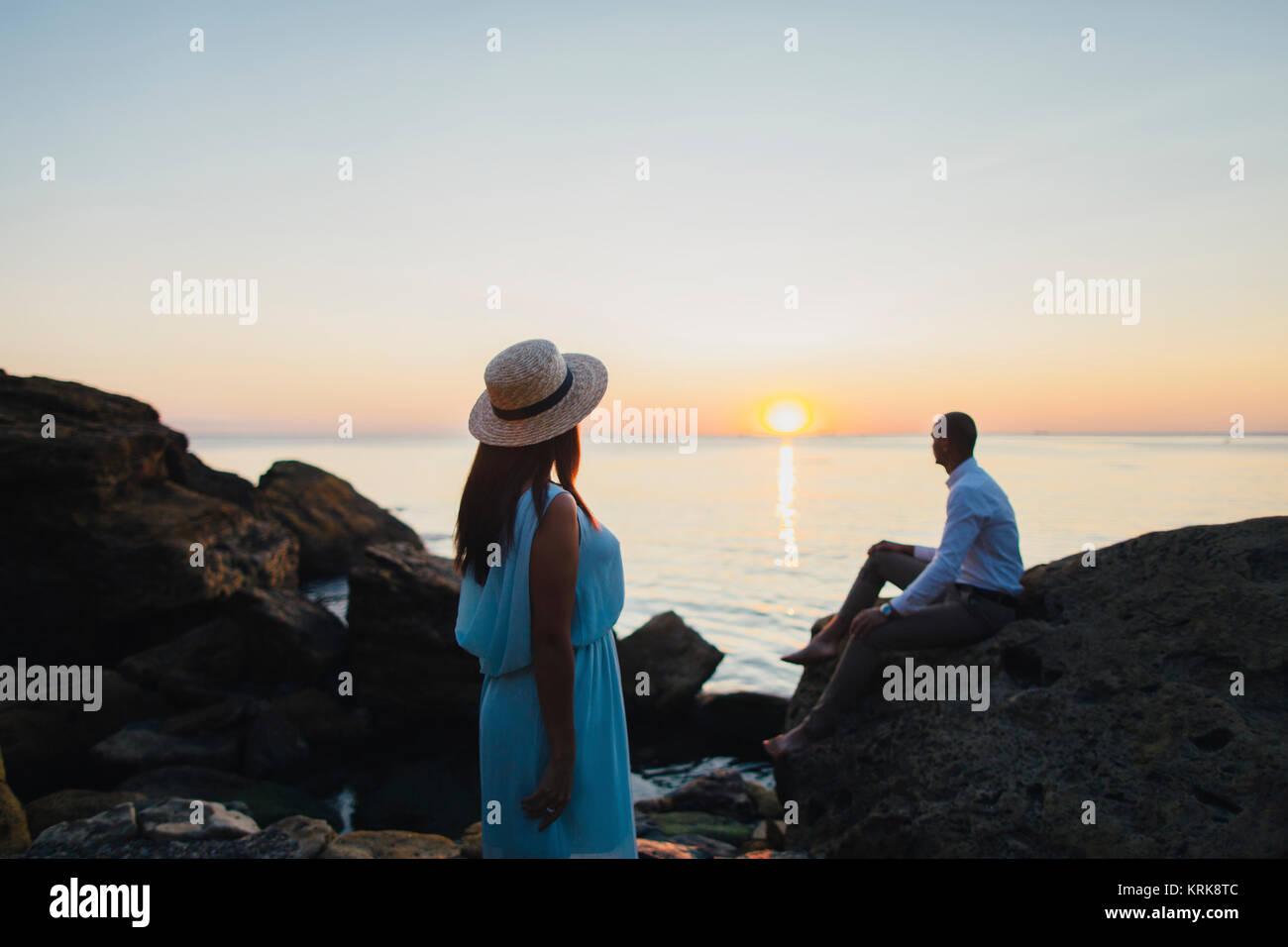 Caucasian couple admiring scenic view of ocean sunset - Stock Image