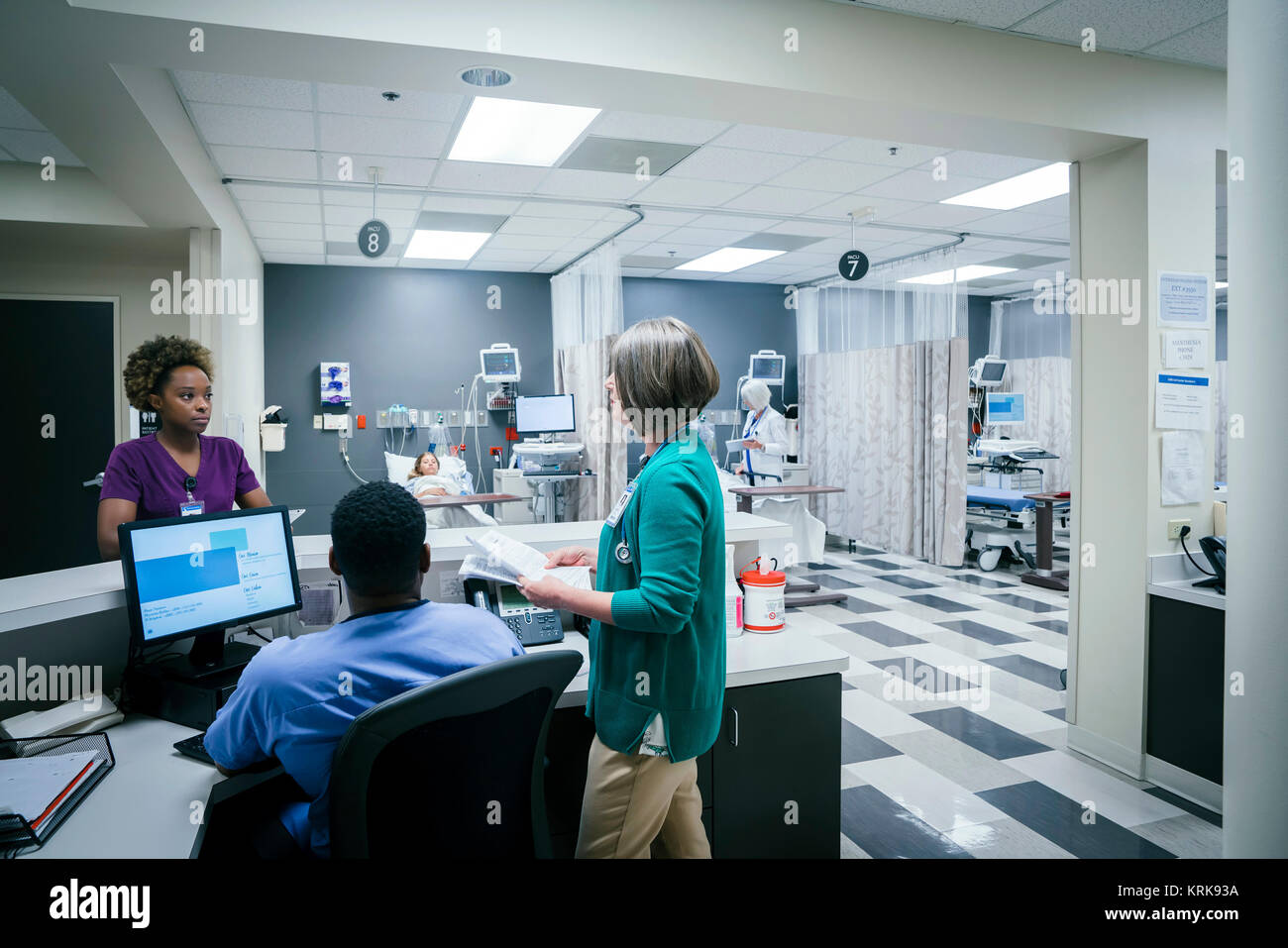 Doctor and nurses talking in hospital - Stock Image