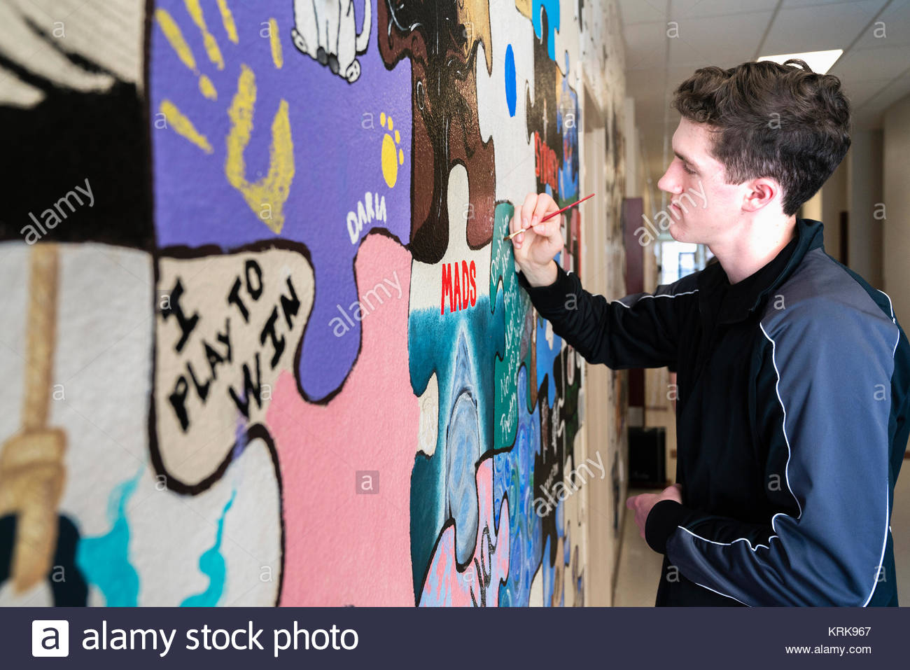 Man painting mural on wall - Stock Image