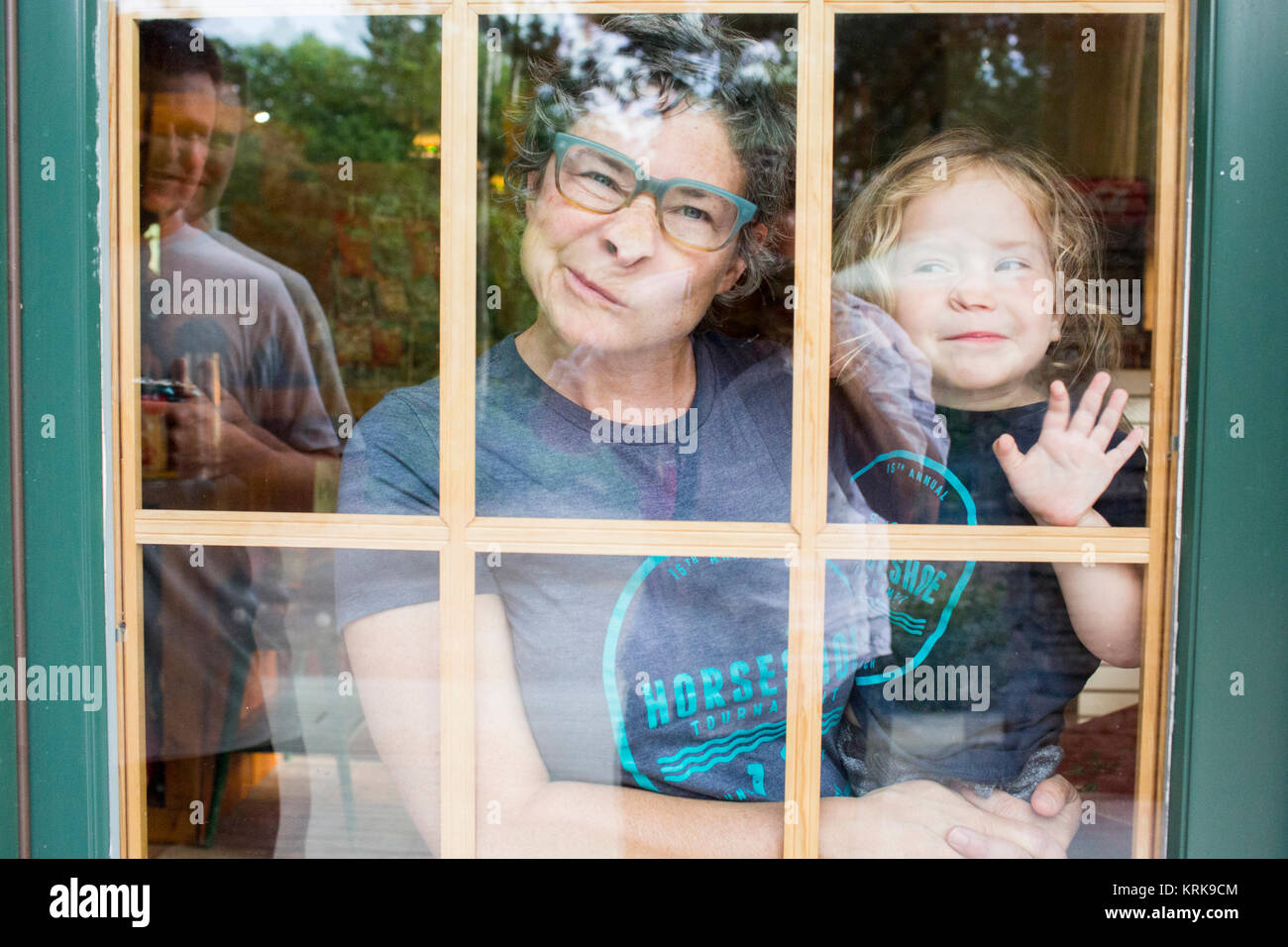 Caucasian mother and son making a face in door window - Stock Image