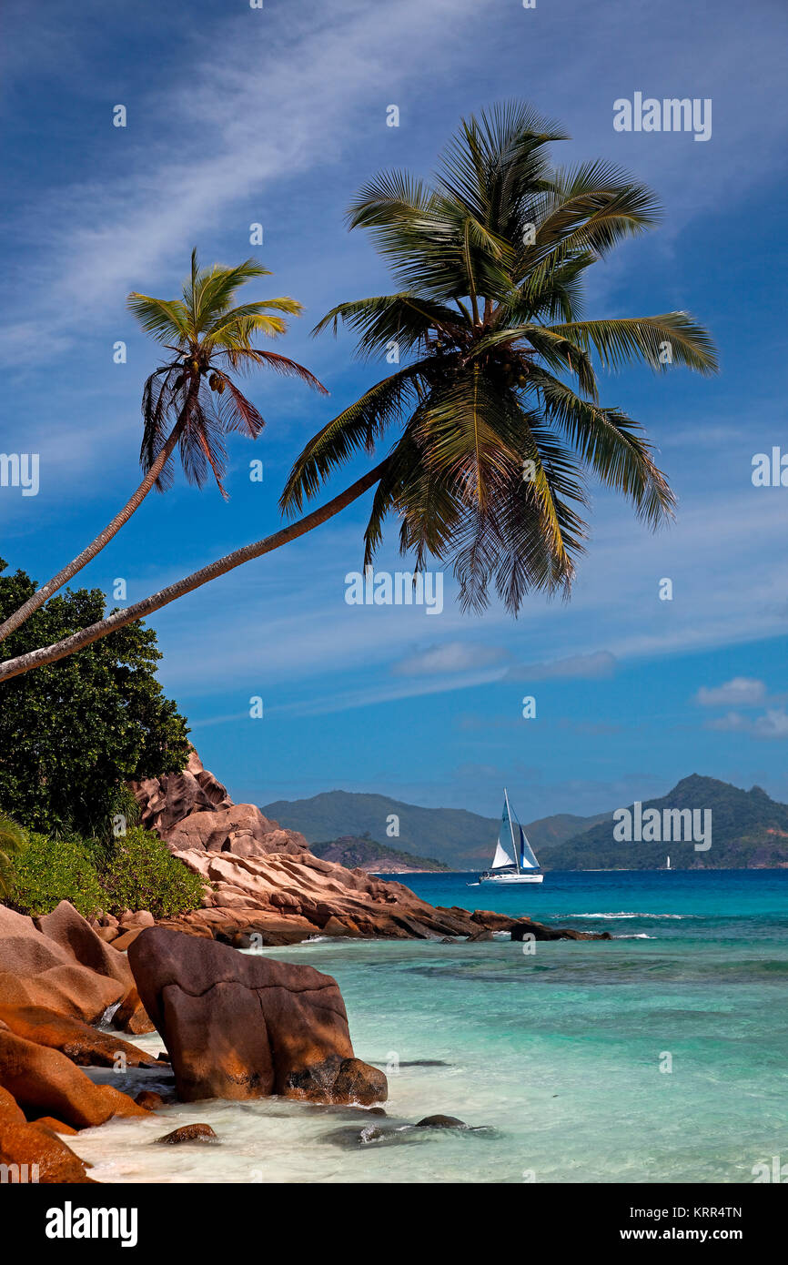 Granite boulders on the shore at Anse Severe , Palm trees, sailing boat, La Digue, Praslin in the back, Seychelles, - Stock Image